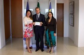 Delegada Carla Patrícia entregando o convite da posse para os desembargadores Valdir Carvalho e Dione Furtado