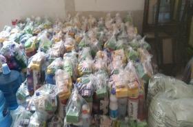 Foto de vários kits de higiene. São sacolas com sabonetes, água sanitária,álcool, sabão amarelo, etc.