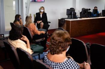 A foto mostra cinco mulheres sentadas, uma delas de toga, em uma sala