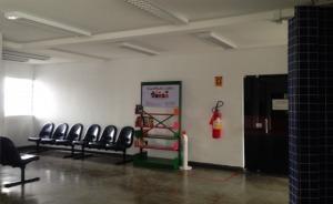 Fotografia de um corredor onde se vê uma estante com livros ao lado de longarinas