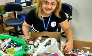 Fotografia de uma mulher segurando caixas e sacolas cheias de frascos e caixas de remédios