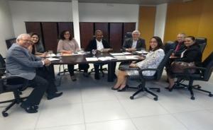 Fotografia de oito pessoas sentadas a mesa de reuniões