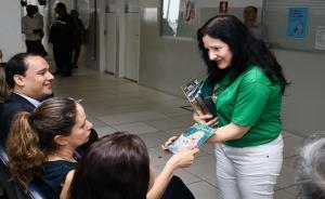 Fotografia da juíza Ana Freitas distribuindo quadrinhos