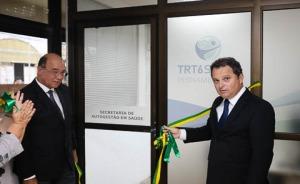 """Foto de dois desembargadores cortando faixa de inauguração na frente de uma porta onde está escrito """"Secretaria de Autogestão e"""
