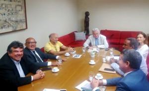 Grupo de oito pessoas, sentadas, reunidas em torno de uma mesa