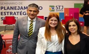 Fotografia com três pessoas no auditório do STJ