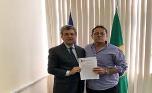 Fotografia de duas autoridades segurando um papel. Atrás delas, estão dispostas bandeiras do Brasil e Pernambuco