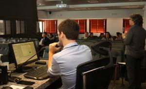 Foto com dois instrutores em primeiro plano e ao fundo plateia com alunos-juízes