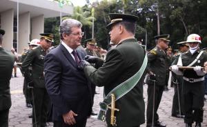 Fotografia de uma autoridade civil recebendo medalha de um comandante militar