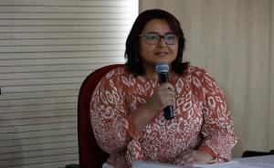 Foto da palestrante Ana Cristina sentada segurando o microfone